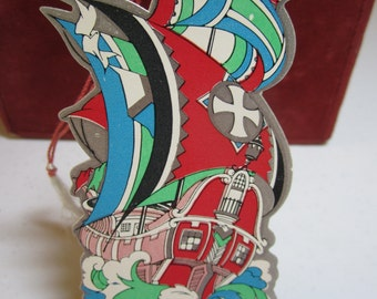 1920's-30's  art deco die cut silver gilded unused nautical themed bridge tally pink and red ship with red blue and green masts gothic cross