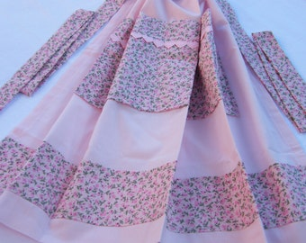 Apron made in plain pale pink with pink and green folral fabric waistband, trim and pocket decorated with pink felt hearts.