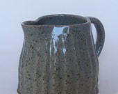 Stoneware fluted jug with celadon glaze.