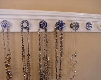 """Necklace organizer. This jewelry hanger has 7 blue and white ceramic knobs on gloss white background 20 """" long. wall storage rack."""