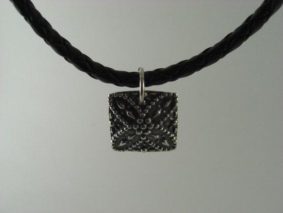 Silver pendant on a black leather cord. Pure silver