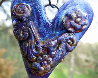 Handcrafted polymer heart pendant  in iridescent blue with flower embellishments