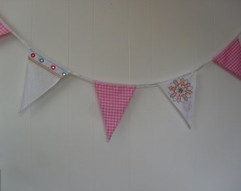 Pink and White bunting. Pink Gingham check. White flags have embroidery and sequins on them.