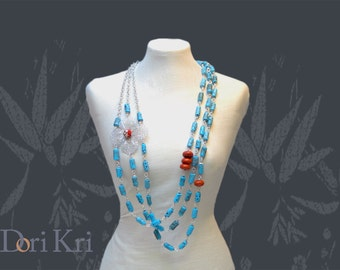 Long statement necklace with silver filigree flower and turquoise stones. Coral beads in a Turquoise necklace. A blue multistrand necklace