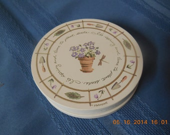 Set of three coasters by Pfaltzgraf, white with garden design on them.