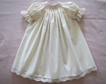 Elegant Ivory Cream and Pink Hand Smocked Bishop Round Yoke Dress for Baby Girl.