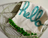 "Say ""Hello"" with this hand made ""Hello"" flour sack towel with turquoise tea-dyed ribbon,  and large pom pom trim"