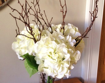 Stunning artificial realistic hydrangea floral arrangements with twigs set in still water, available in either cream or amethyst .