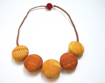 Hand woven orange covered button necklace