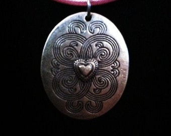 Silver heart pendant on cotton necklace base