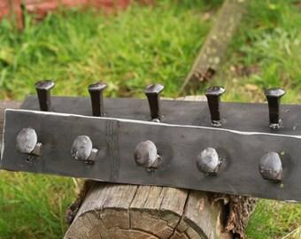 Railroad spike coat rack.  railroad spike heads welded to thick plate steel