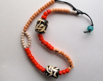 Beaded asymmetrical necklace Native American coral peach and cream colored glass beads African beads on black leather cord