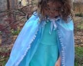 Elsa Inspired Snow Queen Frozen Magic Loop Dress Up Cape Cloak in Ice Blue Satin with Metallic Sheer Overlay
