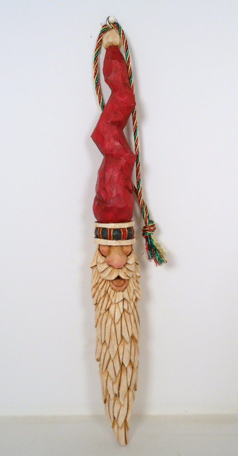 Hand carved wooden santa christmas ornament with a crooked hat
