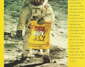 "Amsterdam Airport Shopping Centre Original 1990 Vintage Ad Color Photo Astronaut in Spacesuit on Moon, Yellow Shopping Bag ""See. Buy. Fly."""