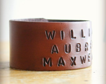 Wide personalized leather bracelet custom stamped with names.