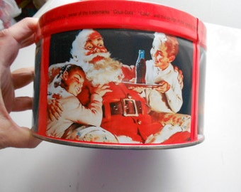 1990 Coca Cola Round Metal Tin Can with Santa Claus and children around it