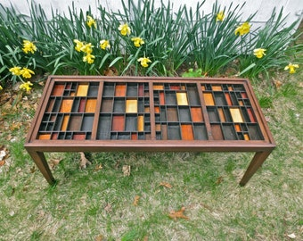 Handmade wood coffee table with a glass table top that lifts out over a top made of  colorful wood blocks in a built in printers type tray.