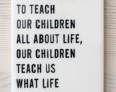 porcelain wall tag screenprinted text while we try to teach our children all about life, our children teach us what life is all... -saroyan