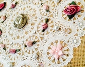 Shabby chic wall art. A fun decoupage collage of a paper doily, vintage broche, ribbon roses, faux pearls & rhinestones on a burlap canvas