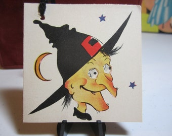 1940's unused A-Meri-Card Halloween bridge tally ugly snaggletooth witch face with hairy warts on her chin and nose crescent moon stars