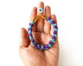 Braided rope bracelet with evil eye charm