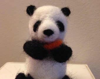 Needle felted panda cub with a carrot