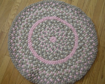 This all-butted round rug is handbraided using new and recycled materials.