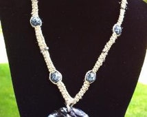"""18"""" hemp necklace with glass peace sign pendant, gray seed beads, and black and white plastic beads."""