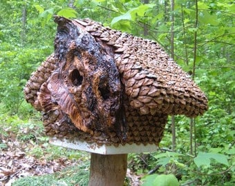 Birdhouse, carved feathers in a wild cherry stump; natural formations creating carved structural birdhouse art; pine cone covered house.