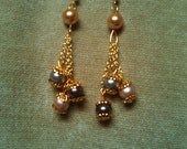 Earrings of 3 strands of gold chain below a rose gold Swarovski pearl bead, with rose, lavender, and burgund beads hanging from the strands