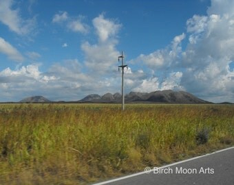 Fine art landscape photograph of telephone pole, grassland with mountains, and blue sky with clouds.