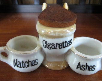 Vintage toilet ashtray with cigarette and match holder