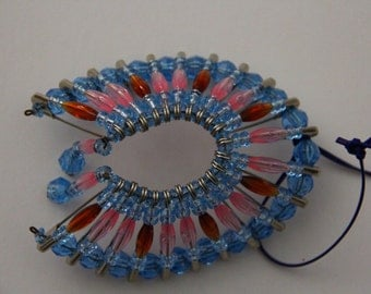 headdress . It is made with Pink and Blue beads and safety pins