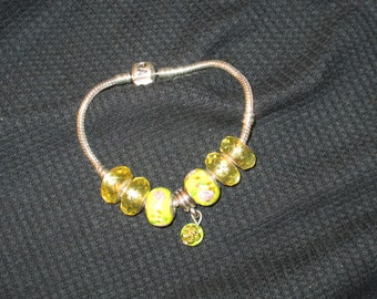 Bracelet-yellow beads with charm.