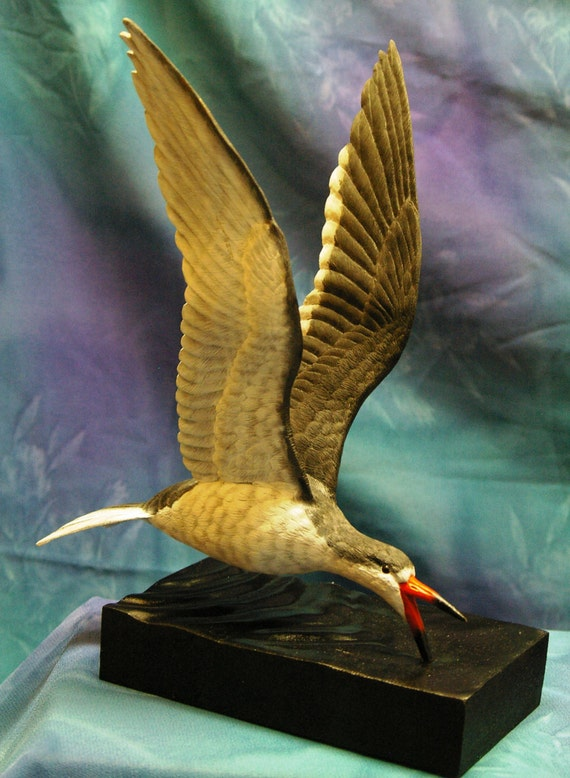 Wood carving of a black skimmer while skimming by glassnwood