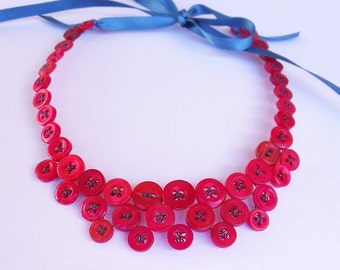 Necklace of red buttons with teal ribbon tie