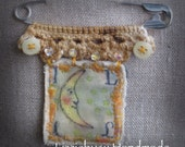 Stitched brooch with crochet lace on a big safety pin  moon colored stamp L luna