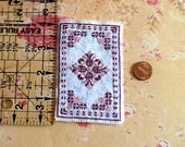 Dark pink and white dollhouse rug