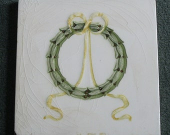 An original Victorian tile of a foliage wreath, berries & ribbons