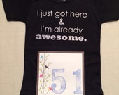 DISCOUNTED -- Nearly Perfect -- #51b, see photos -- I just got here & I'm already awesome.  -- black snapsuit, size 0-3 months