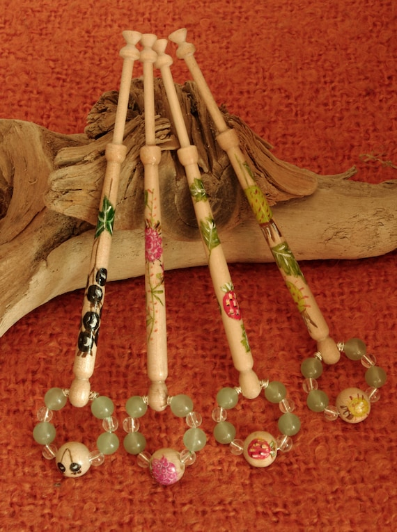 A set of four birchwood lace bobbins with a Soft fruit theme