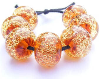 Handmade lampwork bead set of 7 coppery orange and amber glass bubble beads