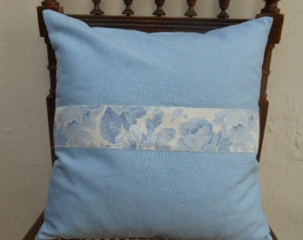 Light blue linen cushion cover with a blue roses pattern