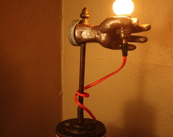 Unique handheld flame tip bulb lamp atop vintage Prince Albert tobacco can.