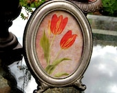 Vintage Silver frame in an oval shape with lovely patina and detailed feet and an easel back, floral image