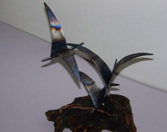 Flock of flying metal birds sculpture