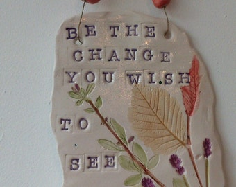 Inspirational quote from Gandhi impressed  with textural leaves and flowers.