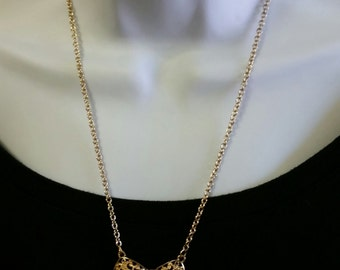 Lovely and classic Holiday bow necklace in gold tone metal