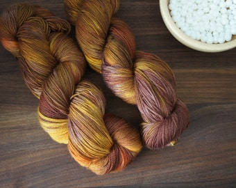 "Hand Dyed Yarn Superwash Merino . Fingering . 440 yards . 100 g . Wild Lilac Moon's Lilac Dream in ""Autumn"" . brown and orange tones"